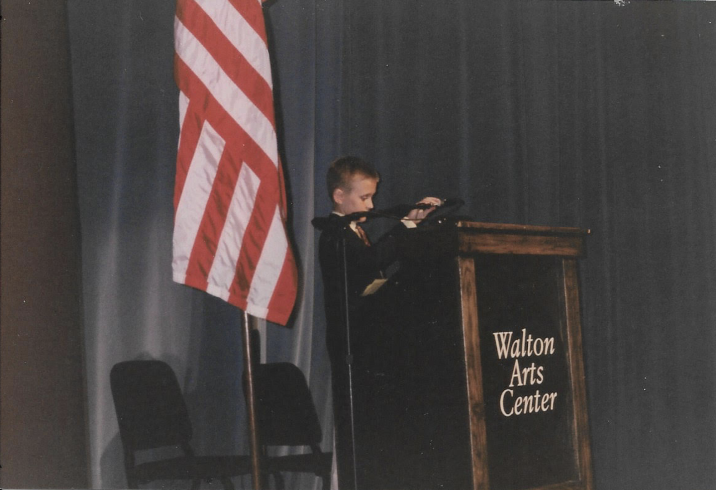 young Justin mertes on stage at school fro talent show with flag in background