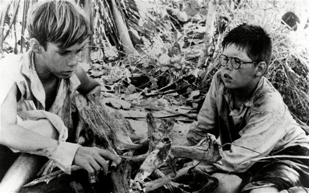 two boys from lord of the flies sitting on ground outside in black and white