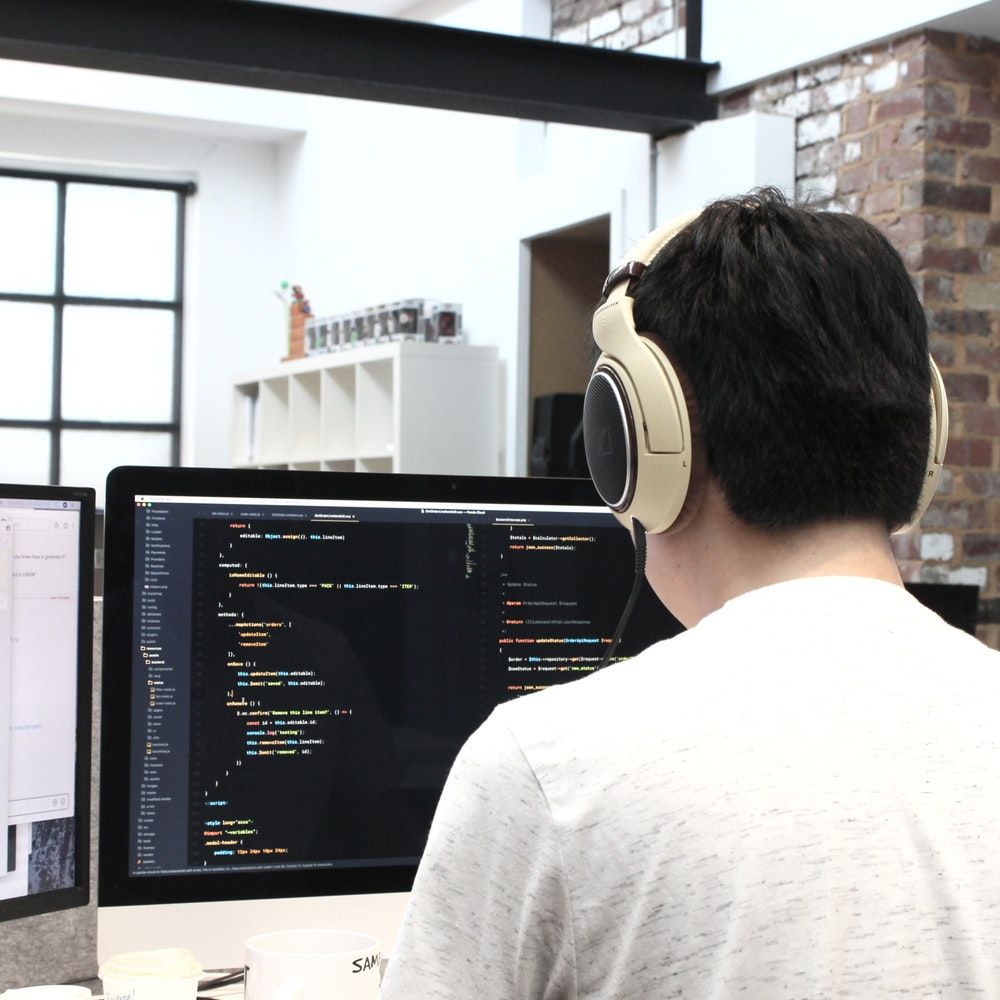 person coding on computer in coffeeshop with headphones