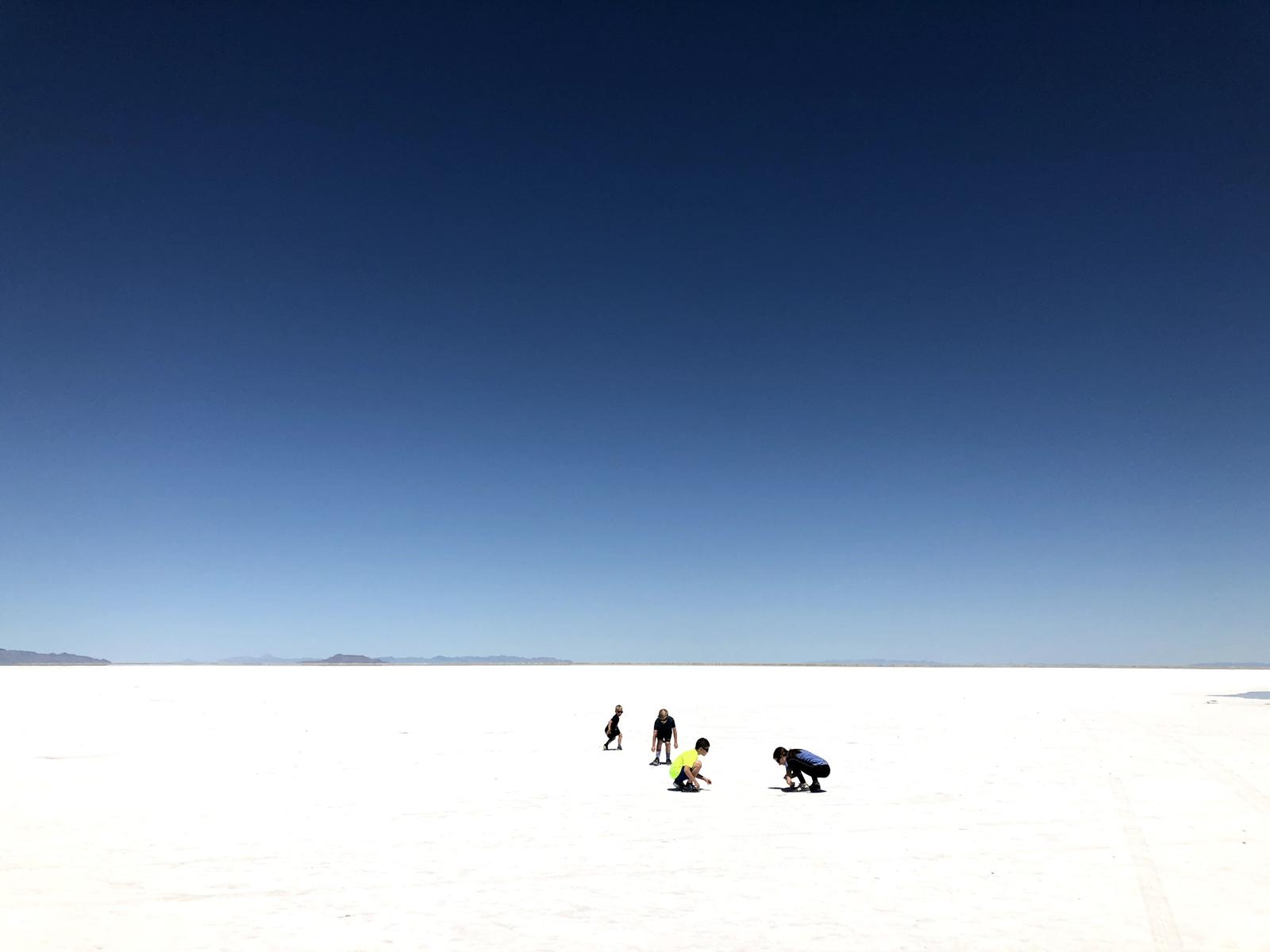 four kids exploring the Bonneville Salt Flats with blue sky