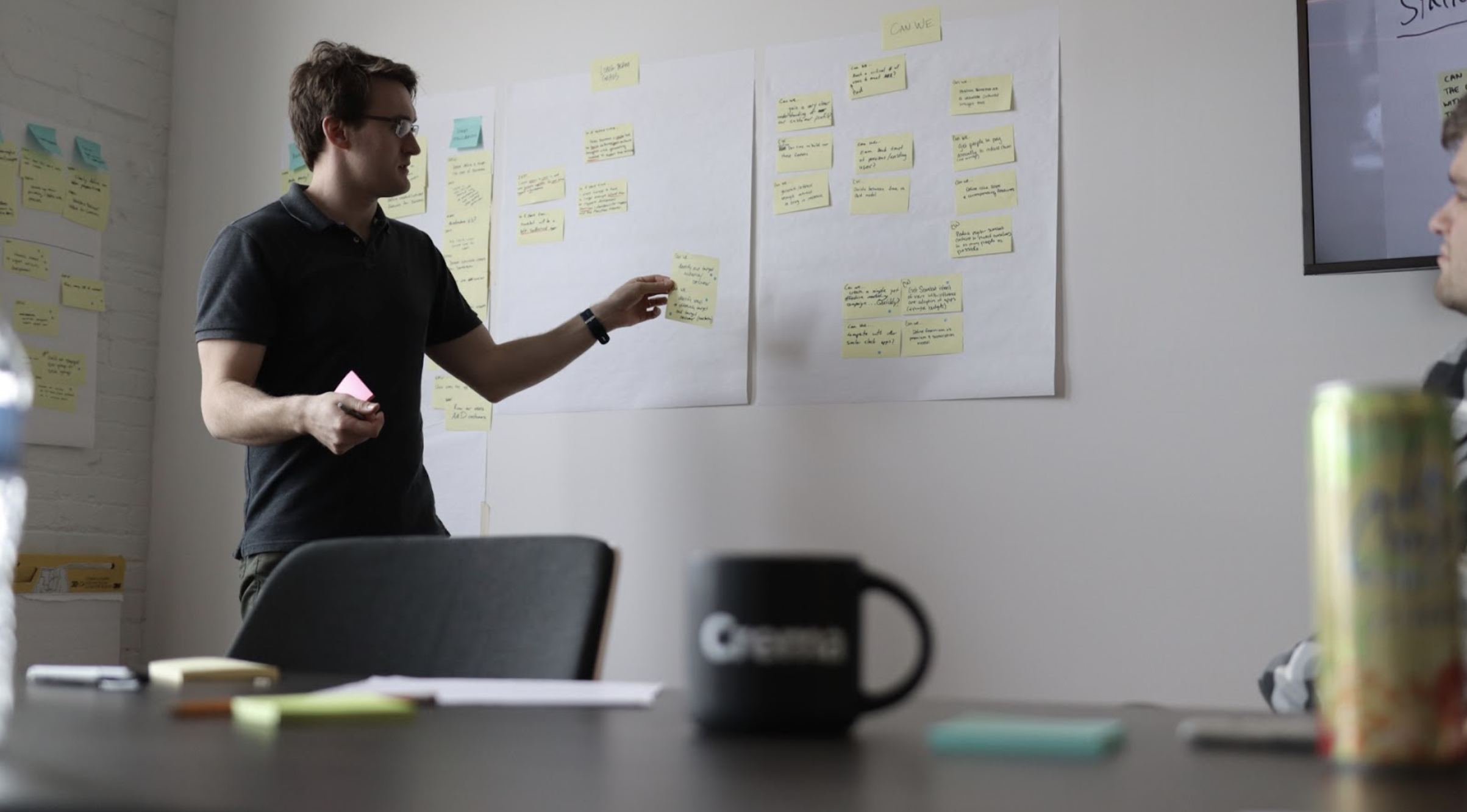 man facilitating design sprint with sticky notes on wall