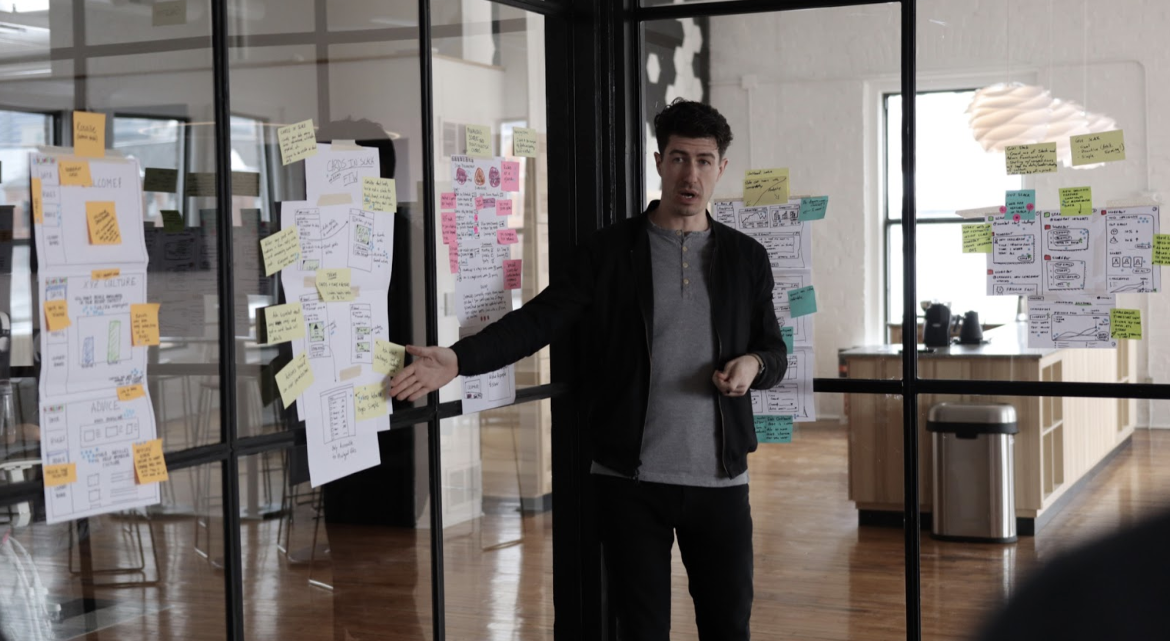 man putting sticky notes up on wall for design sprint