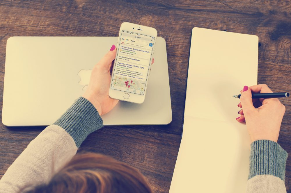 A person copying text to note pad from a mobile