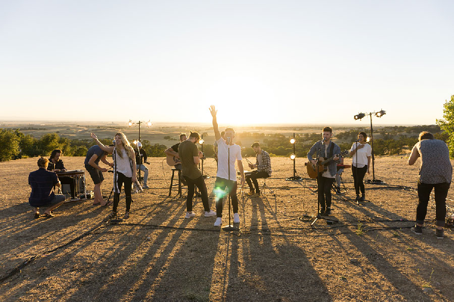 Band Singing in a field in front of a summer sun set