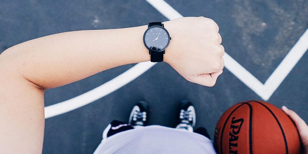 A person holding a basket ball and checking their watch