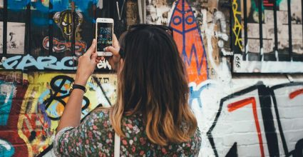 A person taking photos on a phone of graffiti on a wall