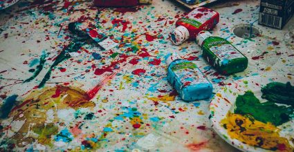A messy artists table covered in multple paint splatters