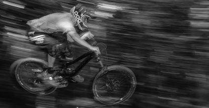 A Person riding a mountain bike down hill with blurred back ground