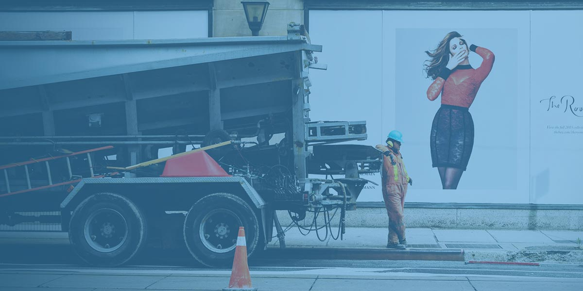 A workman at the back of a truck in front of a Billboard