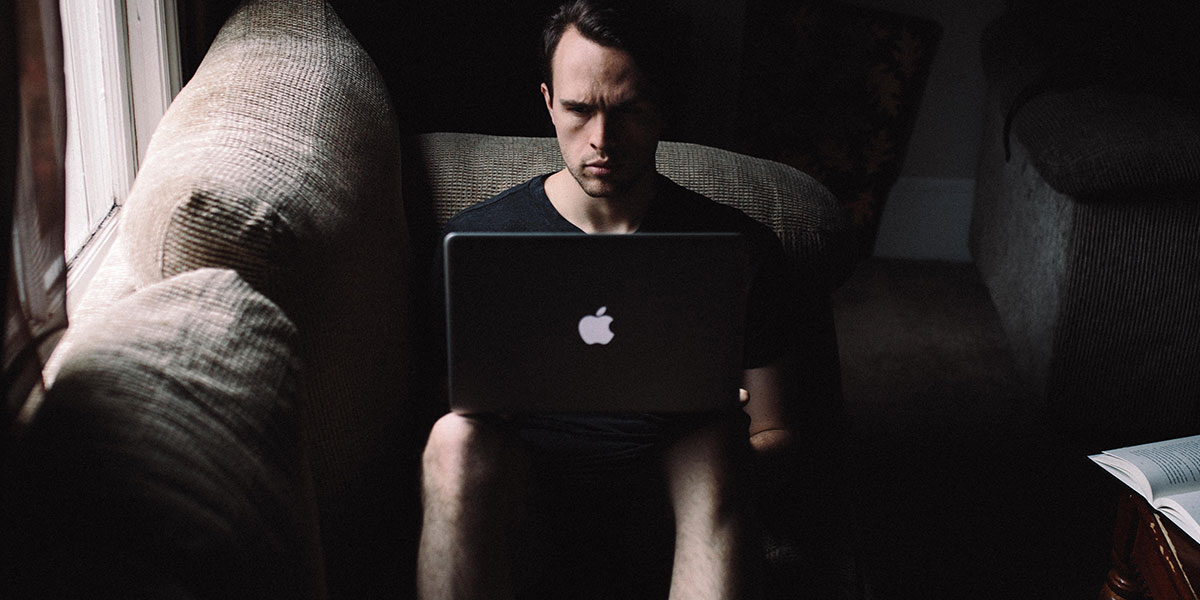 A person working on a laptop in a dark room