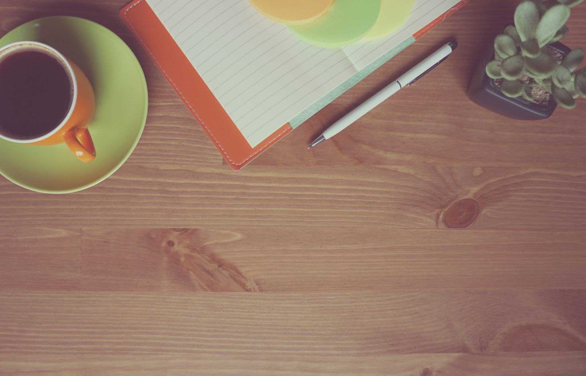 A table with a note pad and cup of coffee