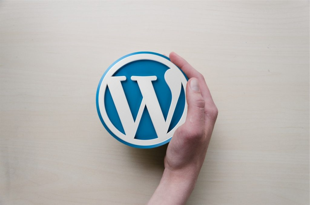 The WordPress logo held in a hand