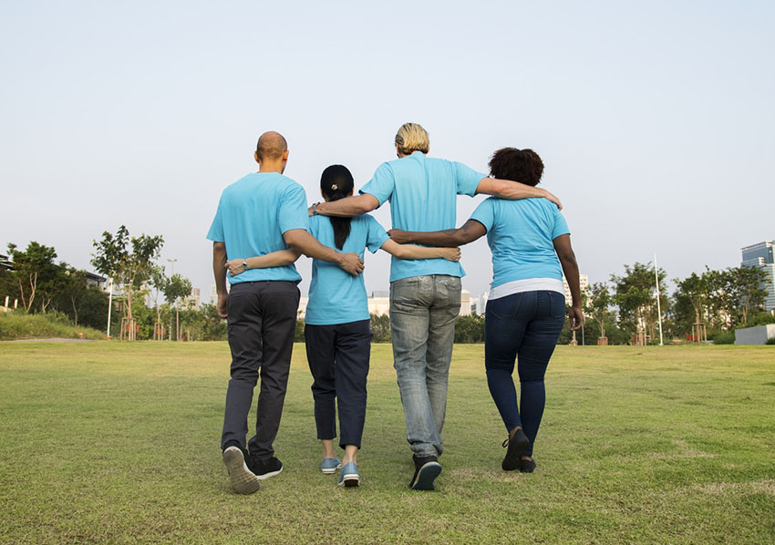 4 people walking along in matching shirts
