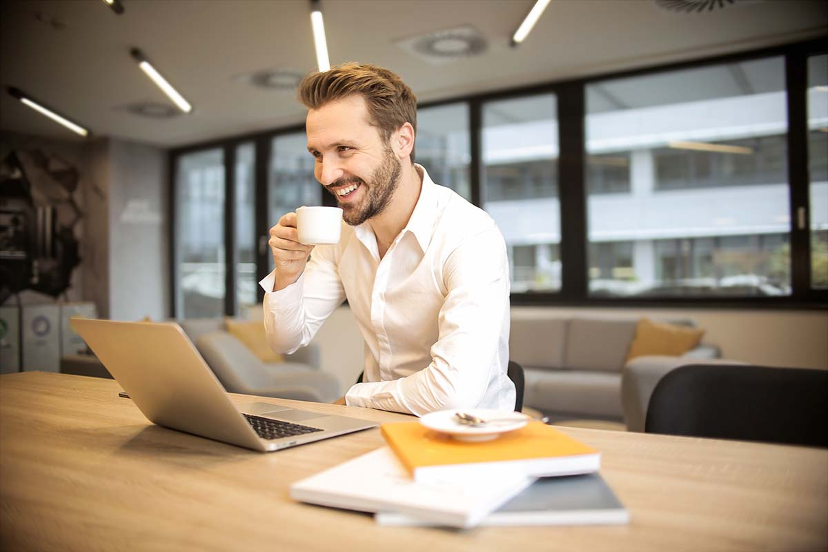 Man smiling drinking coffee in front of laptop
