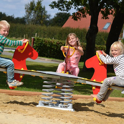 Children Playing On Playground Springer In Sand Pit