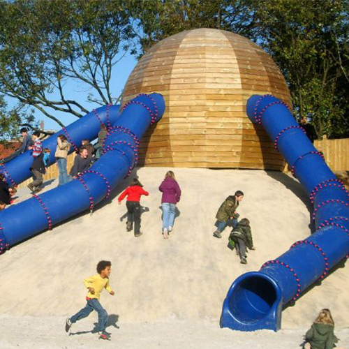 Children Playing On Sand With Outdoor Slide Hut