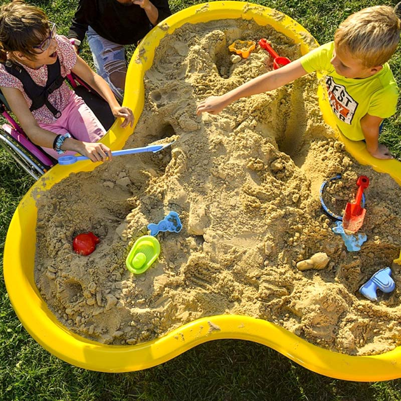 Inclusive play area children playing in sand pit together