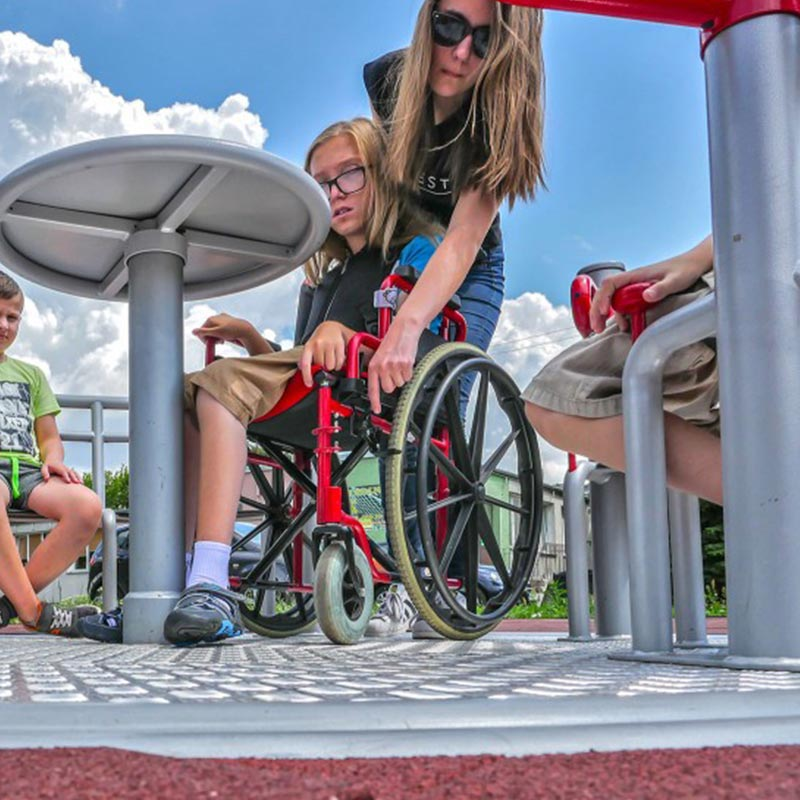 Parent helping child in wheelchair on inclusive play equipment
