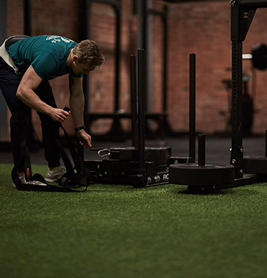 Man setting up equipment in a gym before working out
