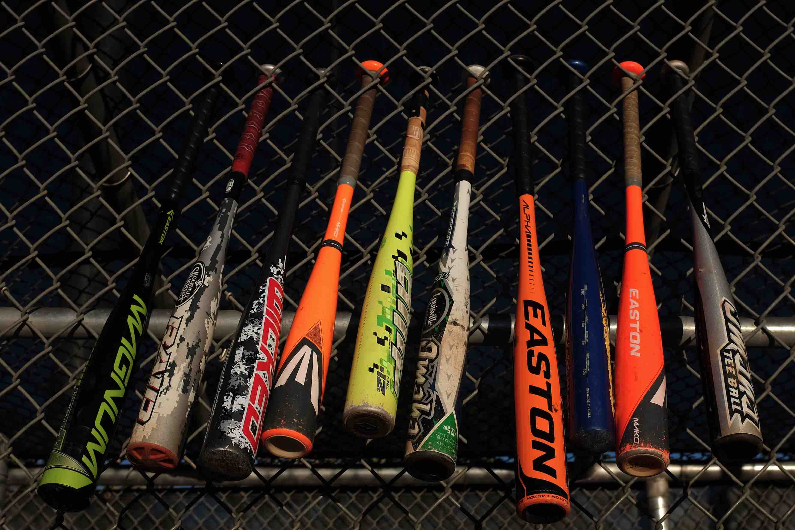 Baseball Bats hanging on a chainlink fence.