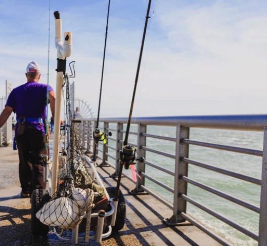 Man hauling fishing gear down a dock.
