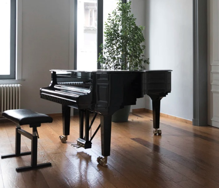 Black piano and bench in a foyer.