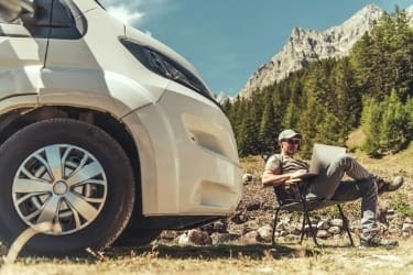 Man working on a laptop next to his RV