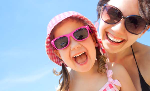 Mother and daughter at the beach smiling