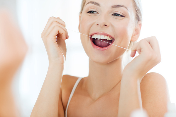 woman happily flossing teeth