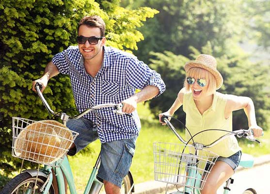 Woman and man riding bikes outside