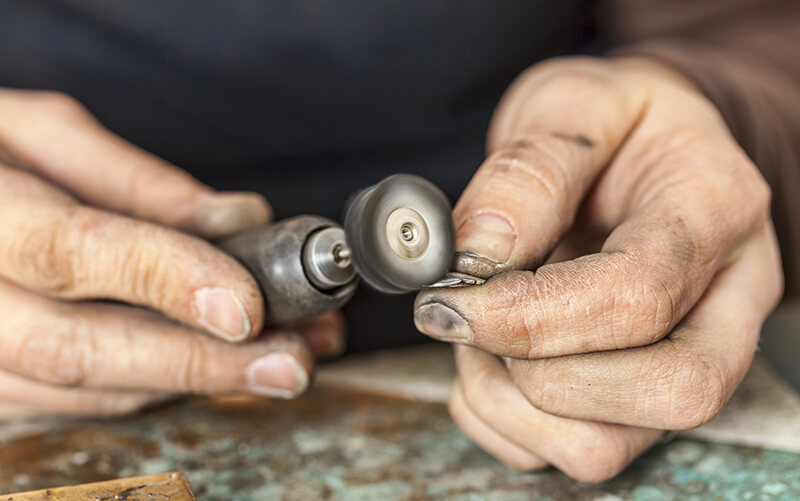 Image of goldsmith creating ring in workshop