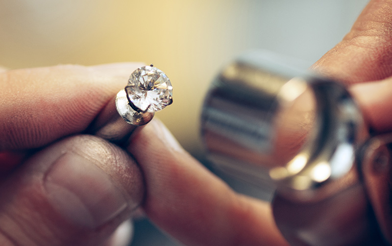 Goldsmith repairing damaged jewellery in workshop