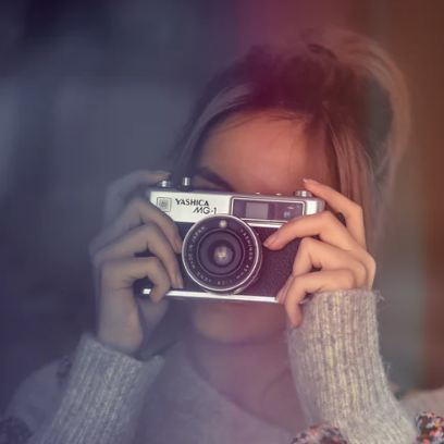 A photographer framing a shot through the rangefinder of a compact Yashica camera