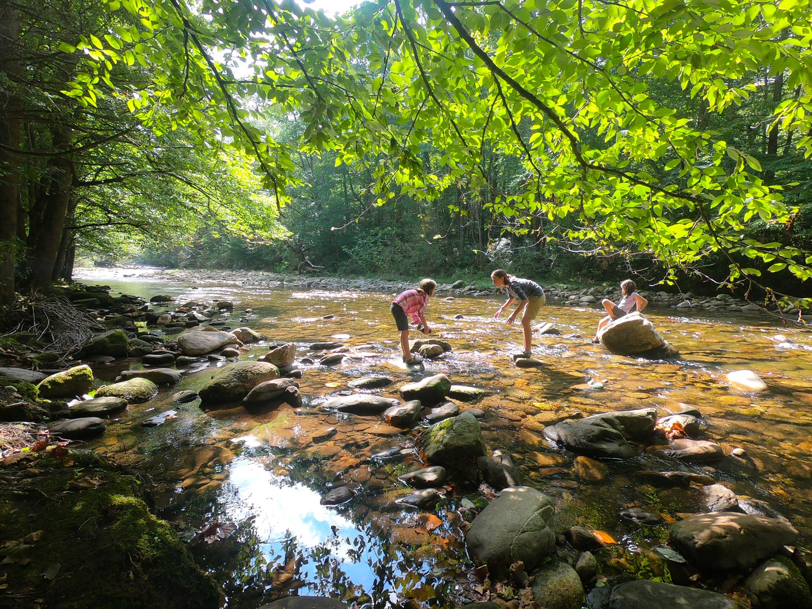 Three girls playing with stones in the Toe River in North Carolina