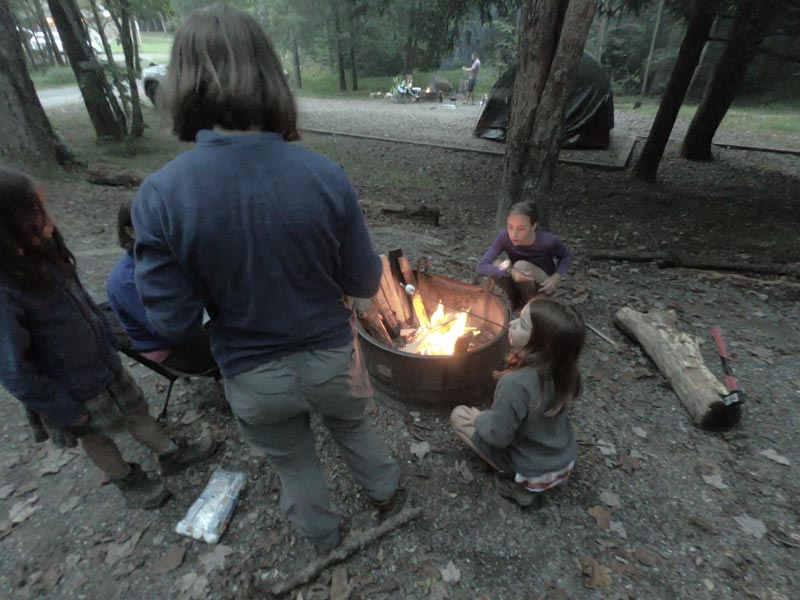 Photo of mother and four daughters building an evening fire at Black Mountain Campground campsite in Pisgah National Forest, North Carolina