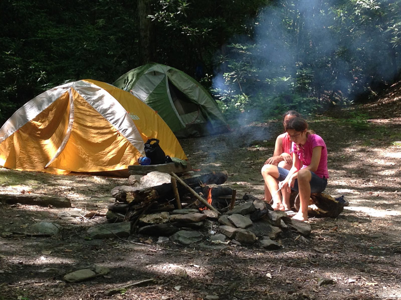 Image of two girls sitting by their campfire with two REI tents, one orange and one green, while camping at Stone Mountain State Park, North Carolina