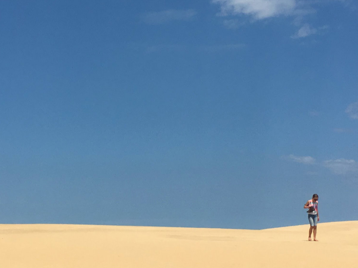Young girl with boots over her shoulder walking barefoot across sand dune at Jockeys Ridge State Park on Outer Banks, North Carolina