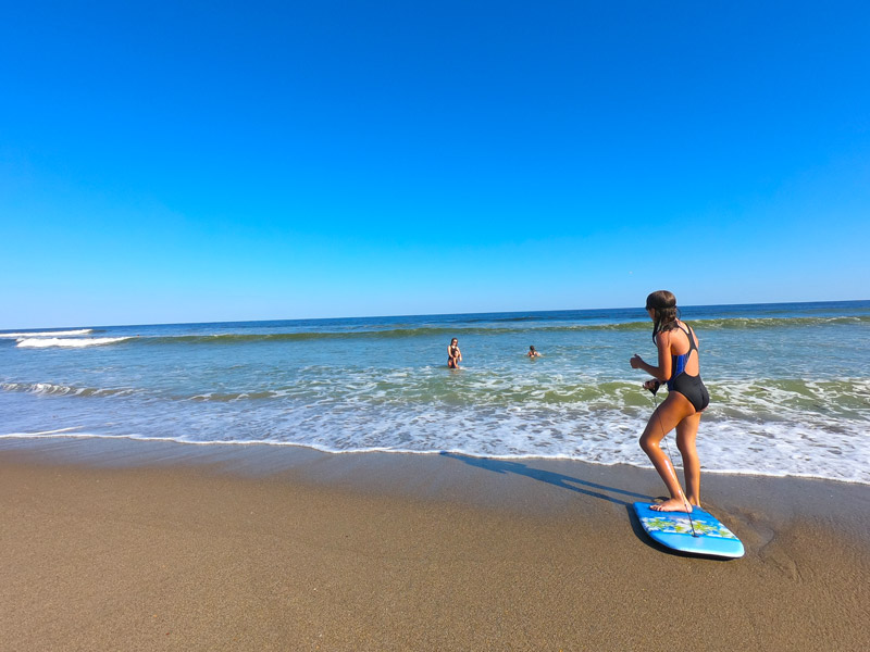 Image of girl on blue boogie board while three sisters swim in the ocean under a cerulean blue October sky on Kure Beach, North Carolina