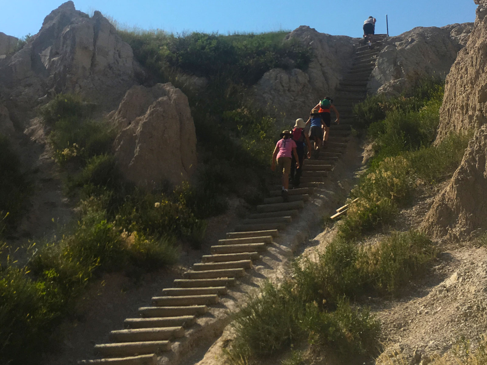 Family hiking ladder on Notch Trail in Badlands National Park, South Dakota
