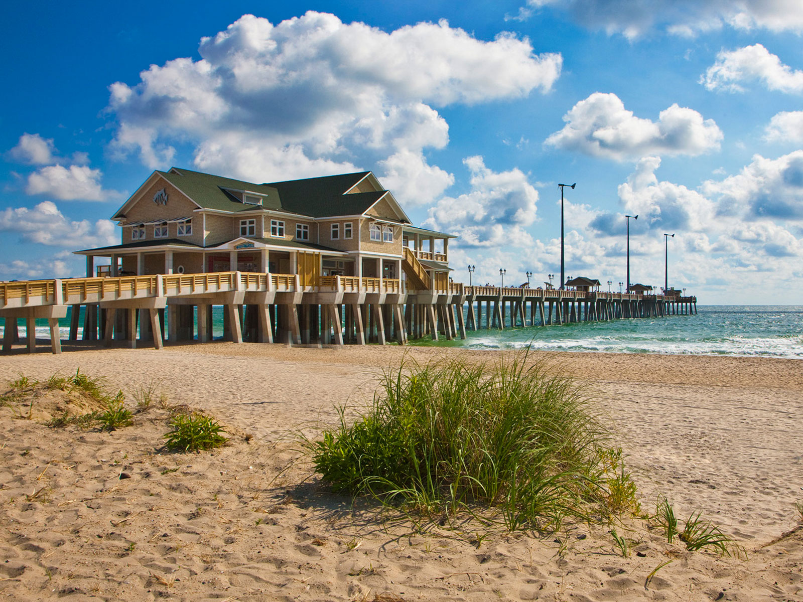 Exterior of Jennettes Pier on a sunny day with blue skies and white clouds at Nags Head, North Carolina