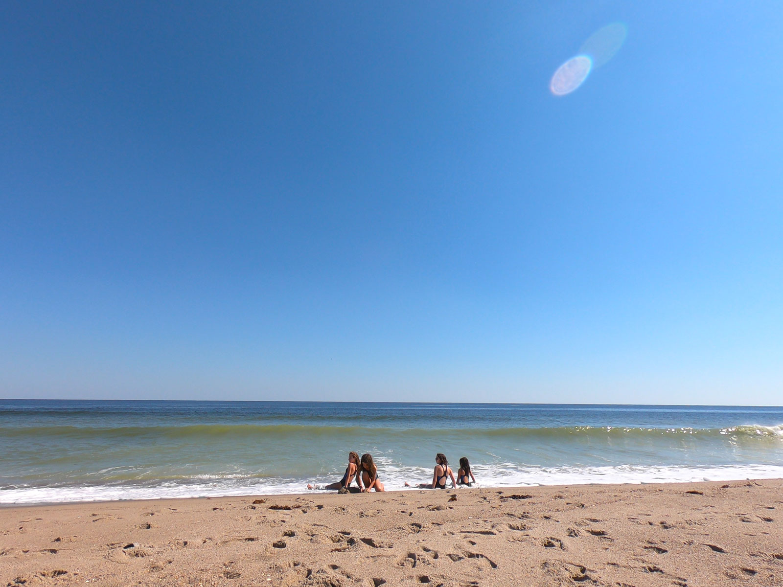 Four girls in the surf under a blue sky at Kure Beach in North Carolina