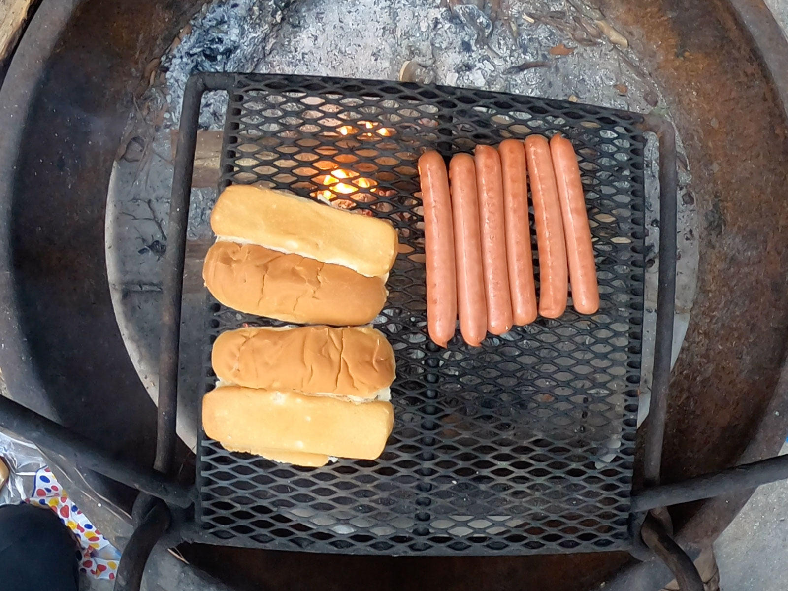 Hotdogs and buns cooking over an open fire at a campsite at Carolina Beach State Park Campground