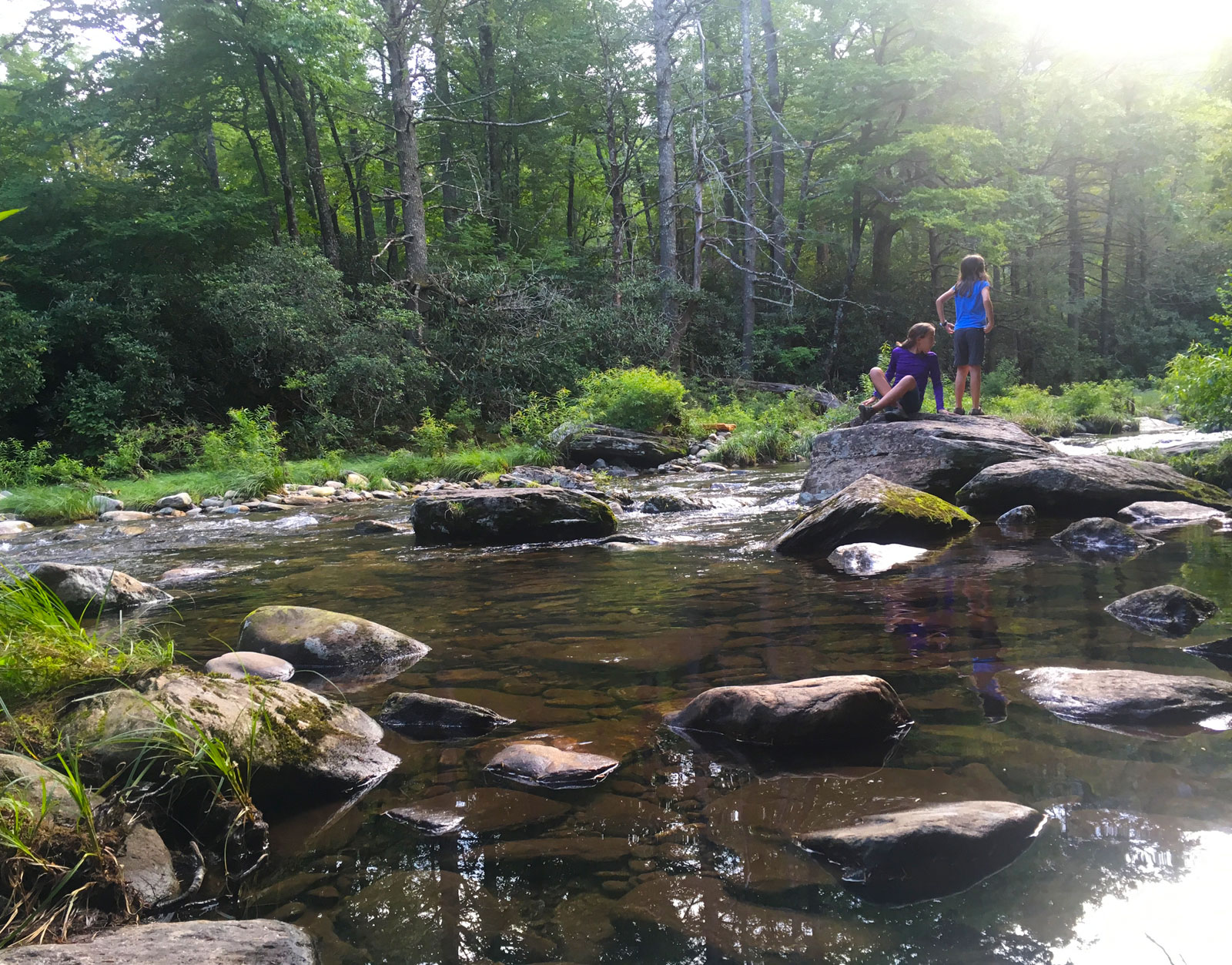Two girls playing on the trail to Setrock Creek Falls in North Carolina