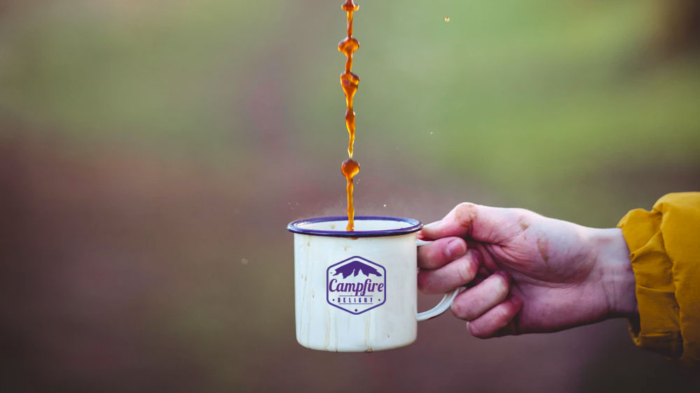 A perfect cup of coffee being poured into a classic camping cup