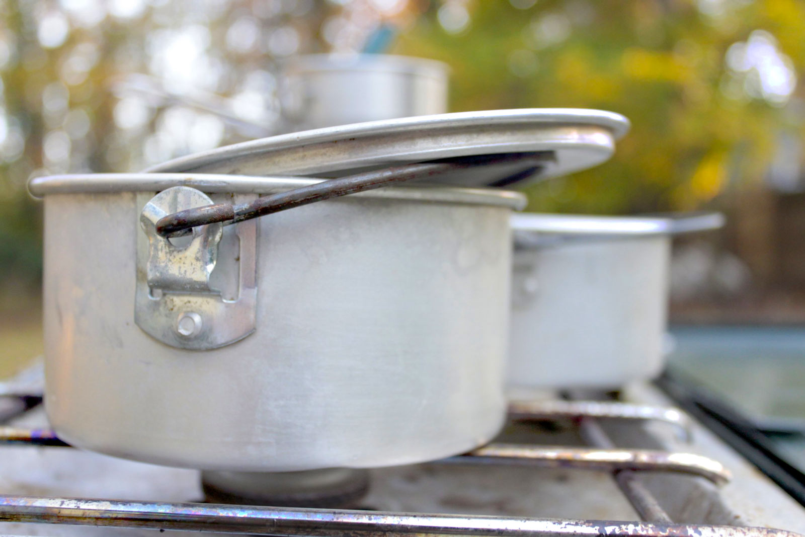 Image of two aluminum pots on a Coleman 2-burner camp stove
