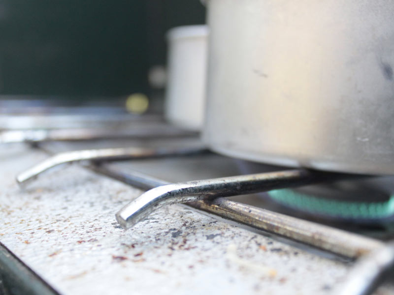 Photo of a Coleman Propane Gas Stove with an aluminum pot on top