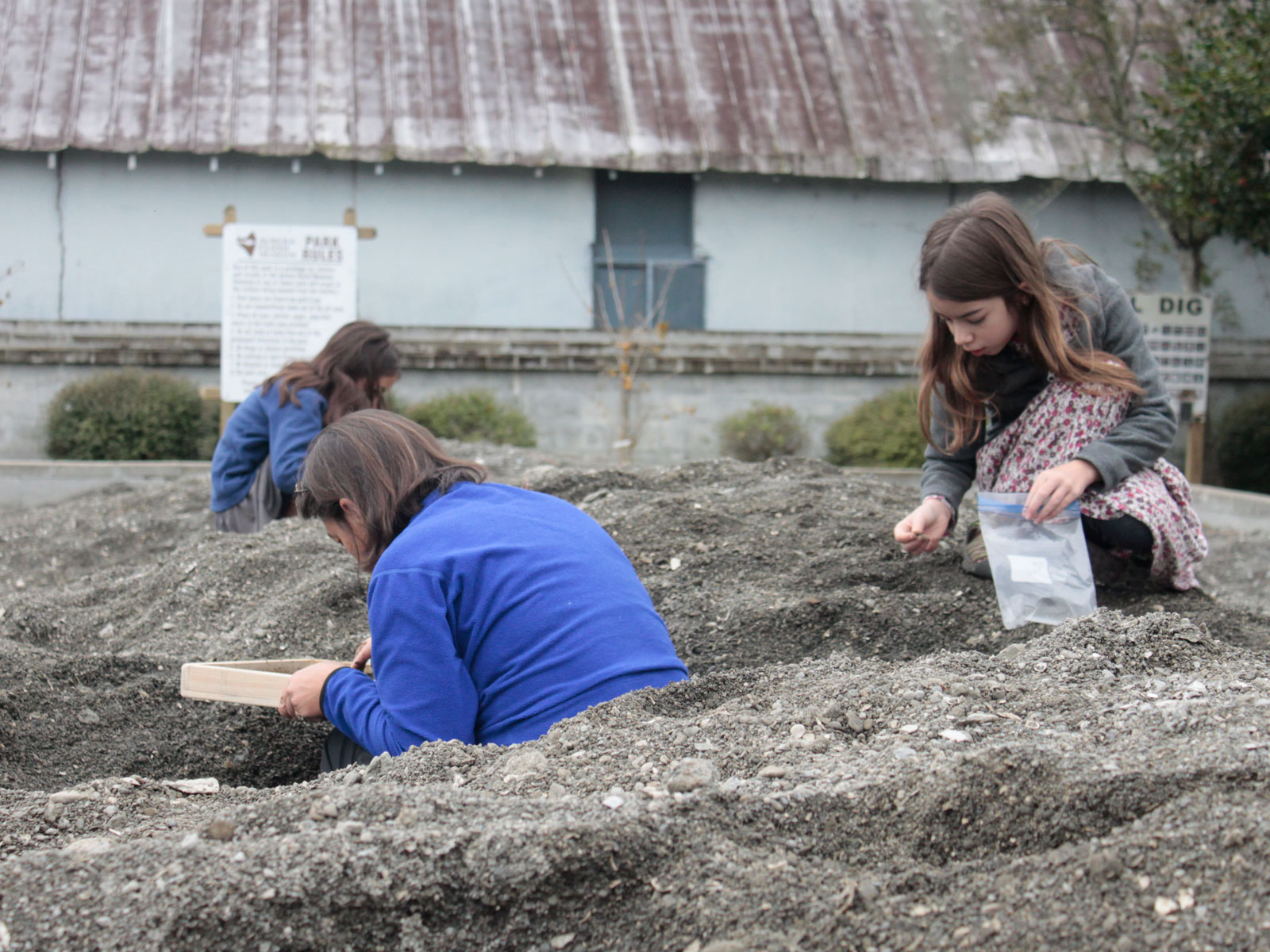 Mother and two girls digging for fossils outside Aurora Fossil Museum in Pits of Pungo in Aurora, North Carolina
