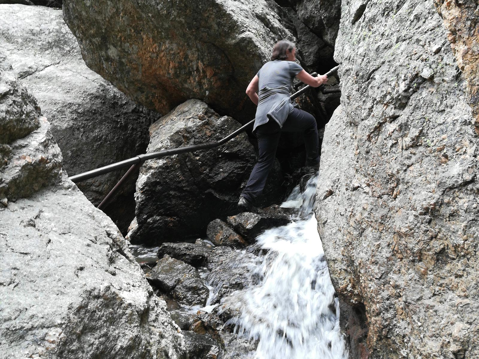 Woman holding onto handrail while hiking up Sunday Gulch Trail through water in Custer State Park, South Dakota