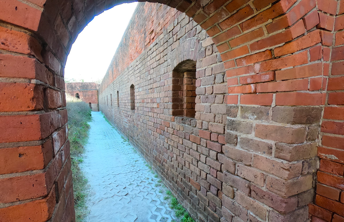 Walking through arched brick walkway and viewing a series of arched brick windows in historic Fort Clinch State Park, Florida, on Amelia Island