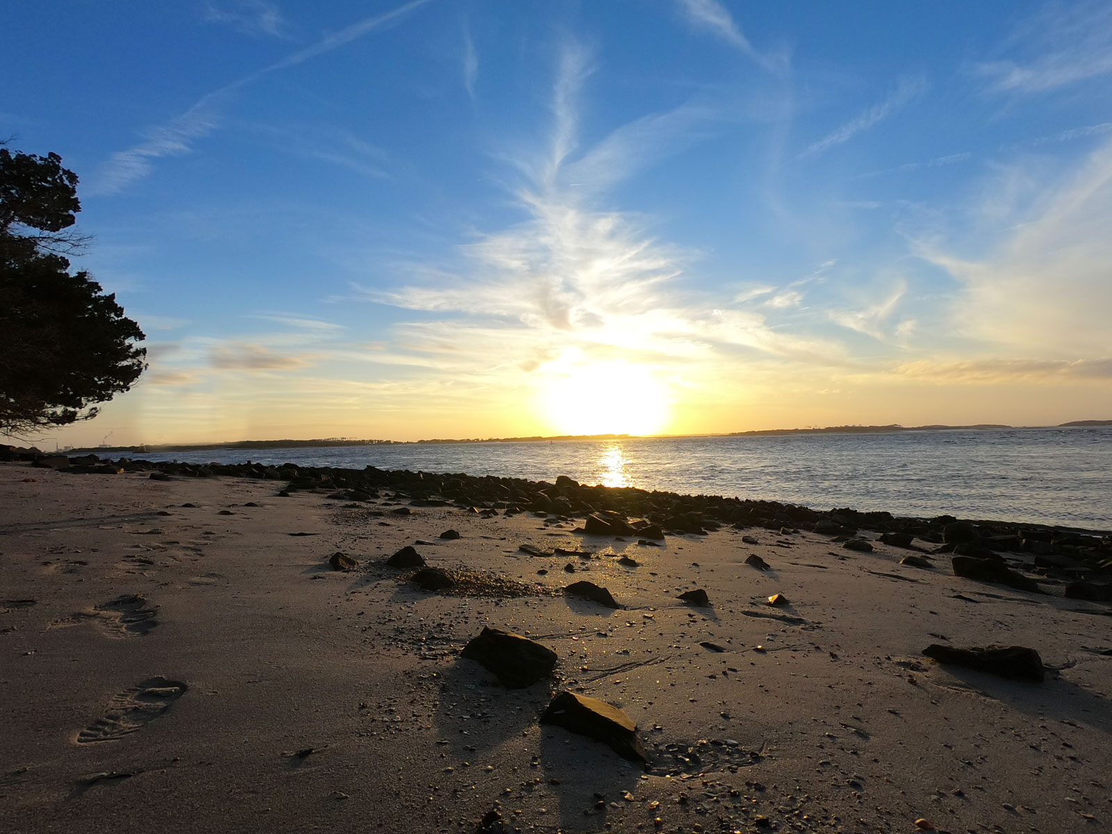 Sunset on Amelia River on rocky shore near Amelia River campground at Fort Clinch State Park, Florida